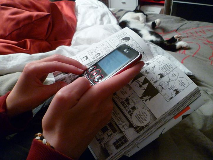 800px-Teenage_girl_texting_while_reading_a_manga_1