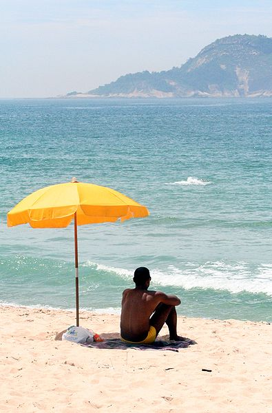 395px-Man_sitting_under_beach_umbrella